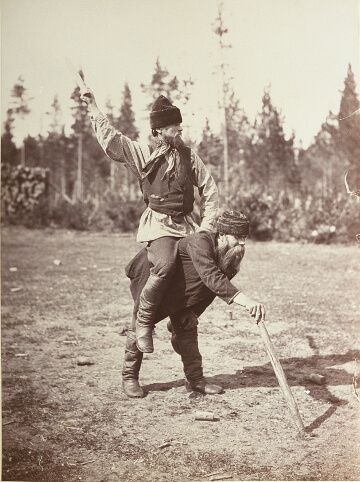A Kyykkä winner rides on the back of a beaten opponent